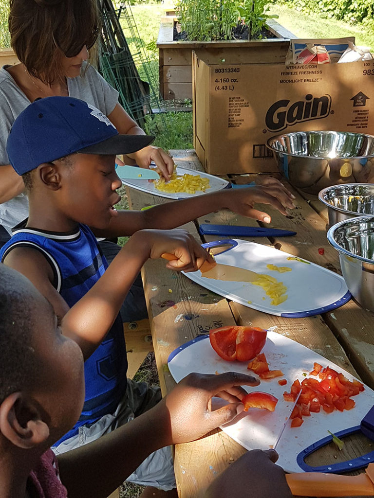 Children chopping peppers at an outdoor table.
